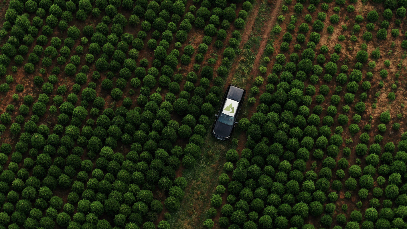aerial photograph of field with pickup driving